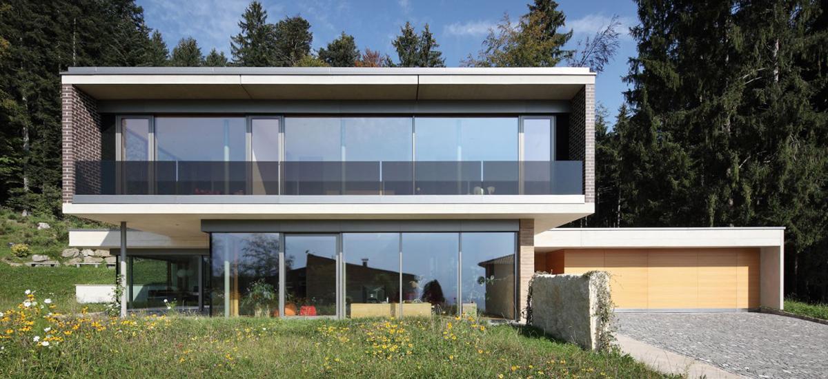 Moderný dom v lese s garážou.